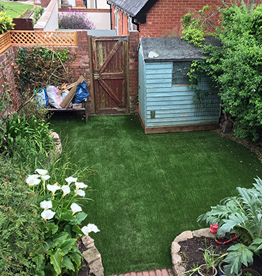 Curved artificial grass area in walled garden