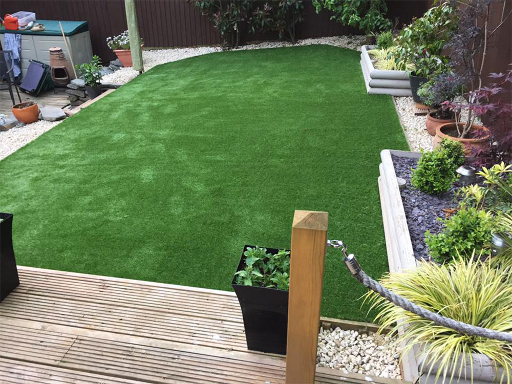 Finished grass next to decking in a back garden