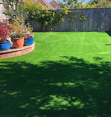 Large, curved lawn in lush back garden